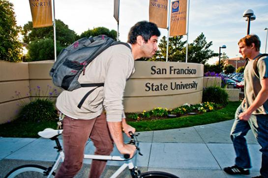 Photo of a student on a bicycle passing an SF State sign
