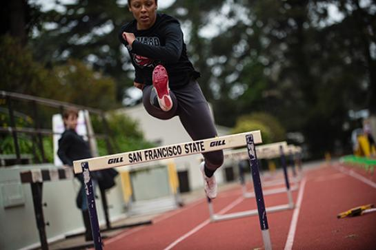 Photo  of a female track athlete jumping over a hurdle